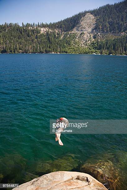 young man diving off of a rock into lake tahoe - emerald bay lake tahoe stock pictures, royalty-free photos & images