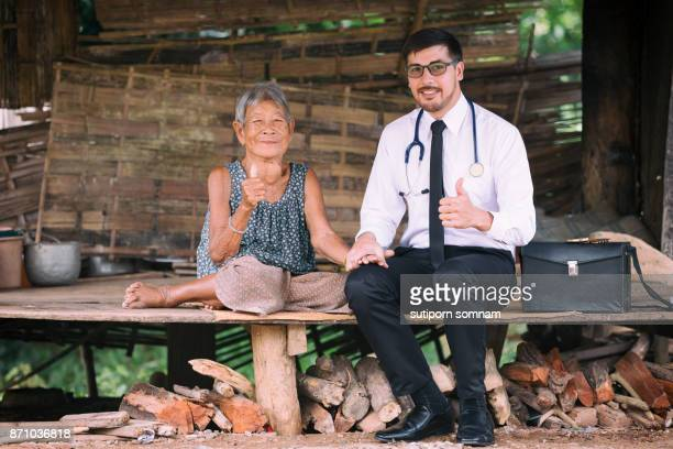 Young man doctor showing hands like to senior patient