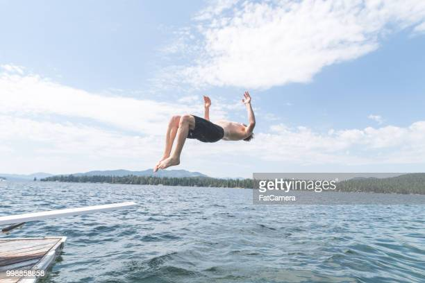 Young man does a backflip into a lake