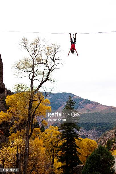 A young man does a bat hang from a slack line after walking the line.