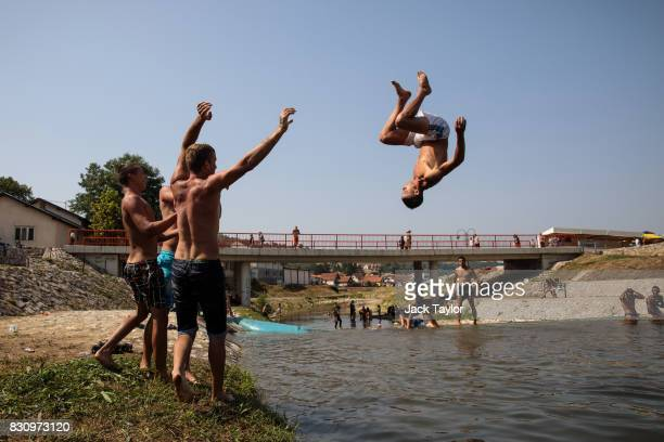 A young man does a somersault as he is thrown by friends into the Bjelica river during the Guca Trumpet Festival on August 11 2017 in Guca Serbia...