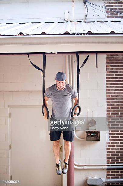 A young man does ring exercises while doing a fitness boot camp.