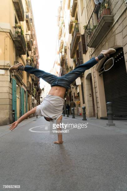 Young man doing a handstand in the city