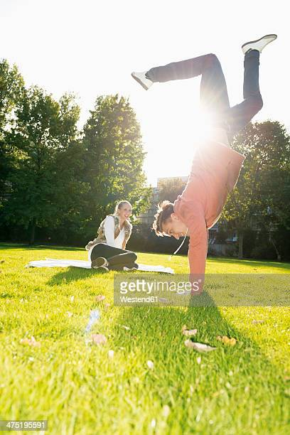 Young man doing a handstand on a meadow