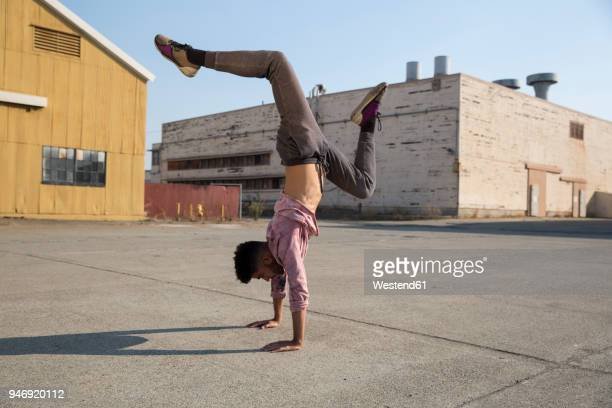 young man doing a handstand outdoors - rébellion photos et images de collection
