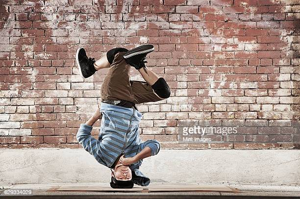 a young man doing a headstand, balancing on his head on a sidewalk. - breakdancing stock photos and pictures