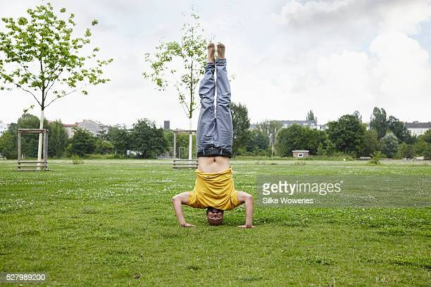 young man doing a headstand in a park