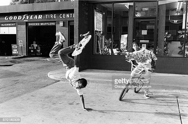 Young man doing a onearm handstand with a skateboard while a friend on a bicycle looks on outside Goodyear Tire Center at 87th Street and Constance...