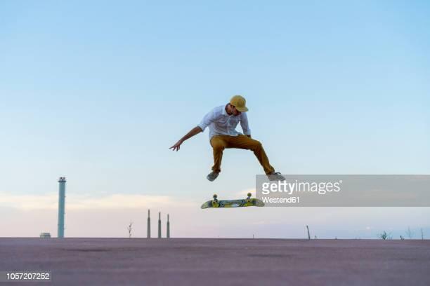 young man doing a skateboard trick on a lane at dusk - truco fotografías e imágenes de stock