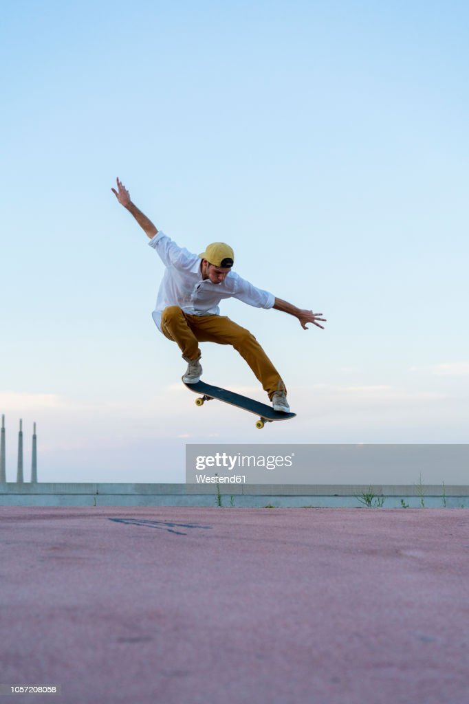 Young man doing a skateboard trick on a lane at dusk : Foto de stock
