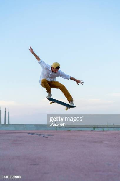 young man doing a skateboard trick on a lane at dusk - human limb stock pictures, royalty-free photos & images