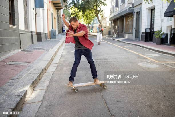 Young man doing a skateboard trick on city street