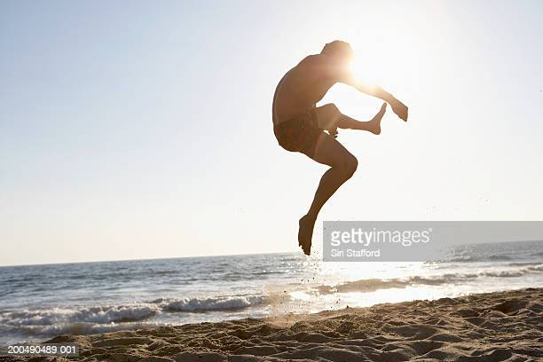 Young man doing acrobatics on beach