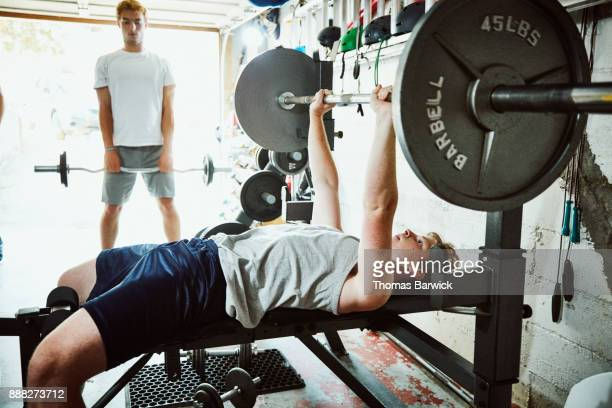 Young man doing bench presses while working out with friends in gym in garage
