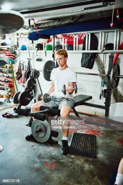 Young man doing bicep curls on bench in gym in garage