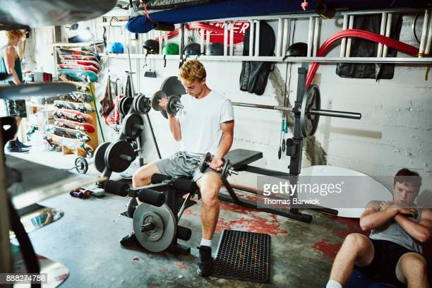 Young man doing bicep curls while working out with friends in gym in garage