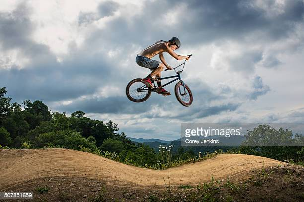 Young man doing BMX trick on rural pump track