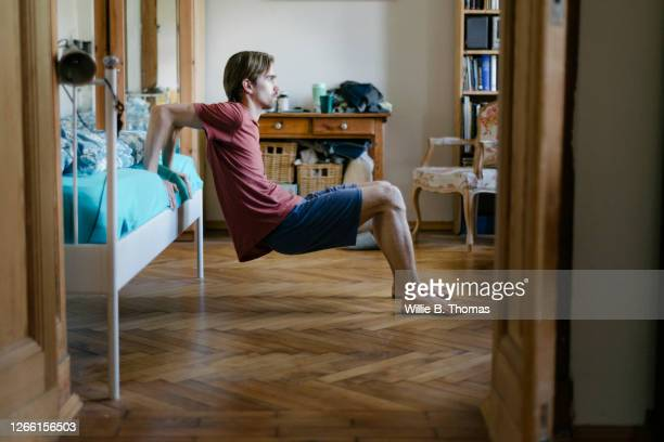 young man doing body weight exercises at home - men exercising stock pictures, royalty-free photos & images