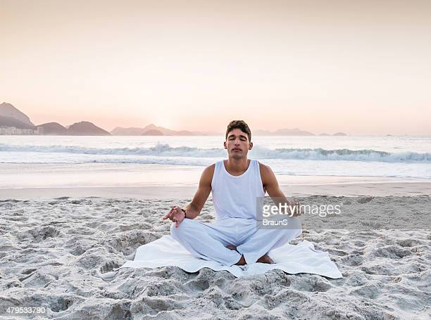 Young man doing breathing exercises at the beach.