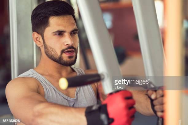 若い男がジムで胸エクササイズ - トレーニンググローブ ストックフォトと画像
