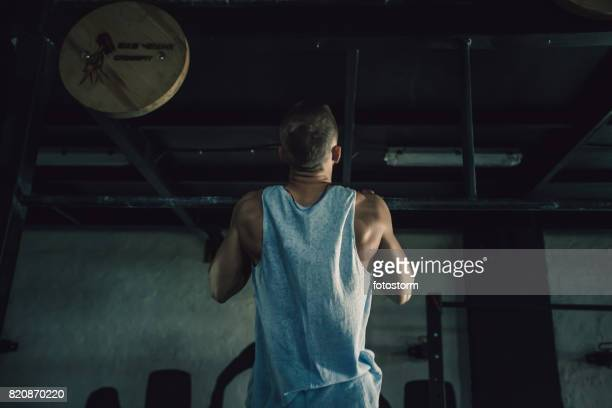 young man doing chin-ups in gym - chin ups stock photos and pictures