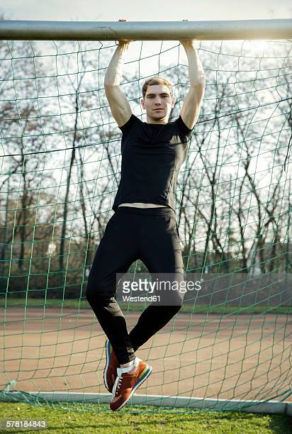 young man doing chin-ups on football ground - goal post stock photos and pictures