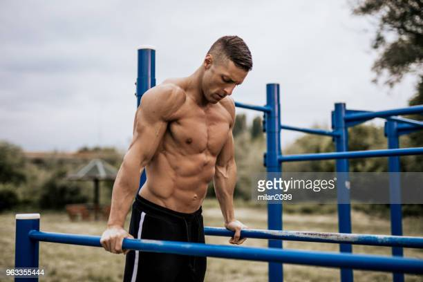 young man doing dips in the local park - muscular build stock pictures, royalty-free photos & images