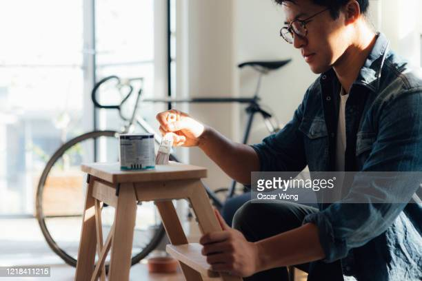 young man doing diy, painting with paintbrush - painting stock pictures, royalty-free photos & images