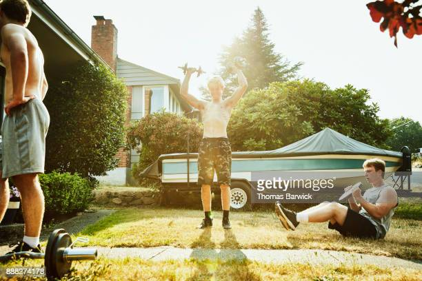 Young man doing dumbbell presses while working out with friends in front yard on summer evening