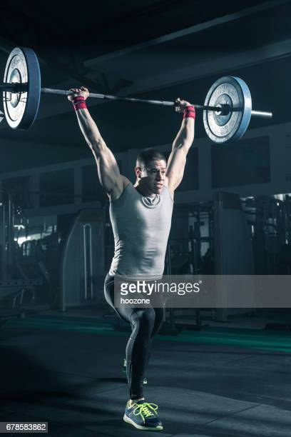Young man doing exercise with weights