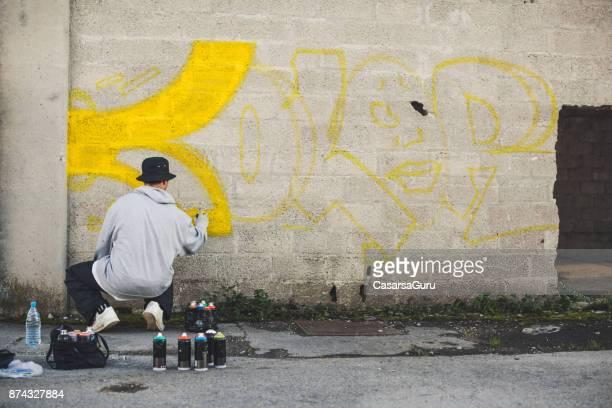 joven haciendo graffiti - oficio artístico fotografías e imágenes de stock