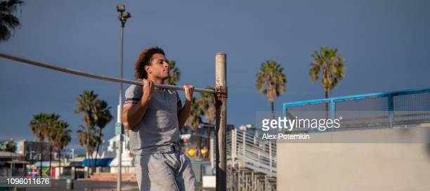 young man doing gymnastic exercise on the chin-up bar - alex potemkin or krakozawr latino fitness stock photos and pictures