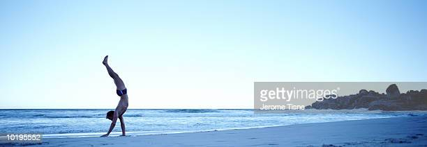 young man doing handstand on beach - young men in speedos stock pictures, royalty-free photos & images