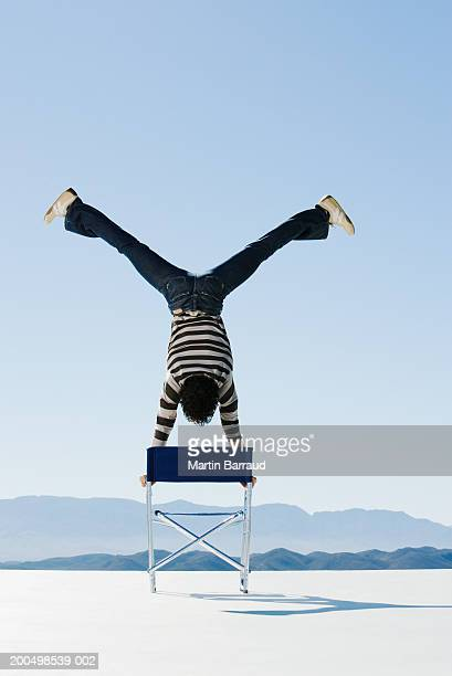 Young man doing handstand on chair, legs apart, outdoors