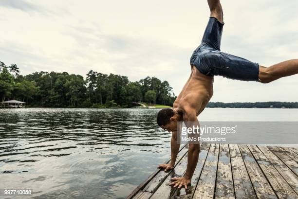 young man doing handstand dock at