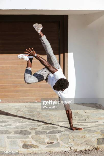 young man doing handstand on footpath during sunny day - casual clothing photos et images de collection