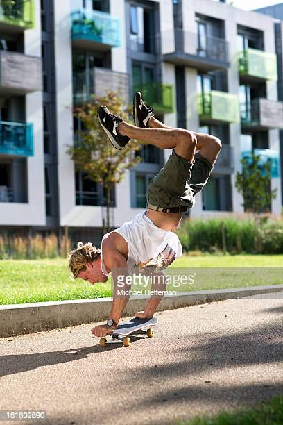 Young man doing handstand on skateboard
