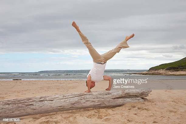Young man doing handstand on tree trunk at beach