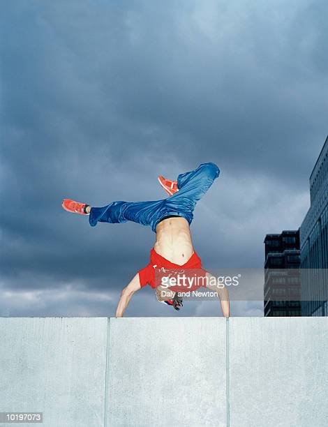 Young man doing handstand on wall