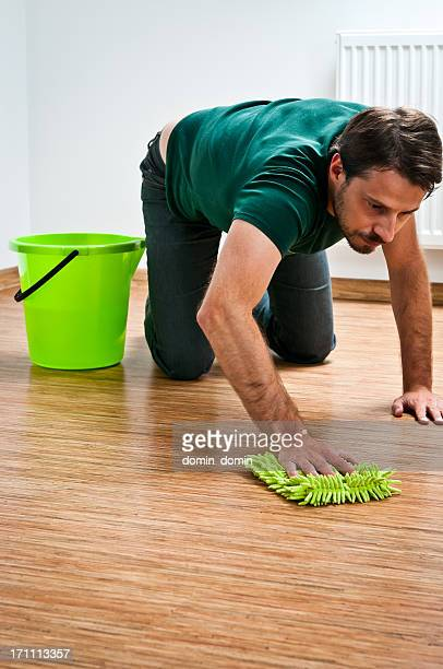 young man doing houseworks, man is cleaning wooden floor - daily bucket stock pictures, royalty-free photos & images