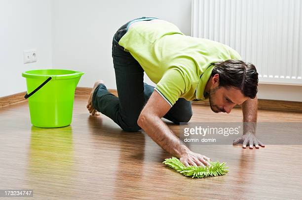 Young man doing houseworks, man is polishing the floor