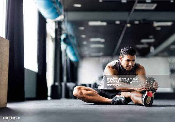 young man doing leg stretches in the gym - sports training stock pictures, royalty-free photos & images