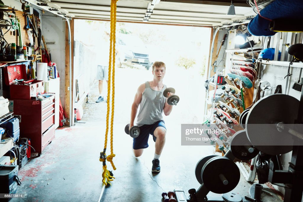 Young man doing lunges with dumbbells in gym in garage : Stock Photo