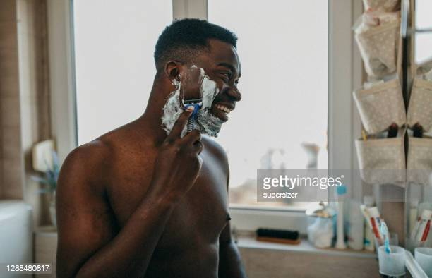young man doing morning rituals - shaved stock pictures, royalty-free photos & images