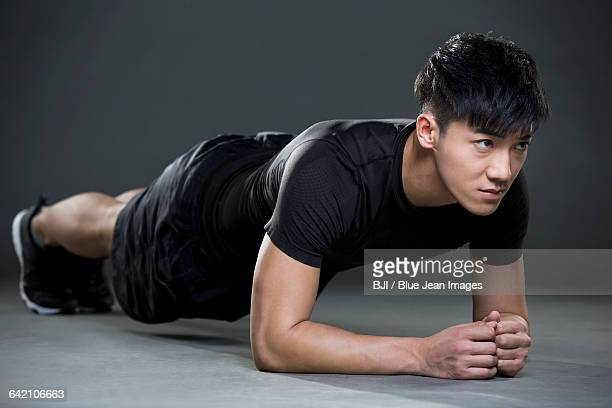 Young man doing plank exercise