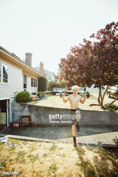 Young man doing plyometric exercises on wall of driveway in front of home on summer afternoon