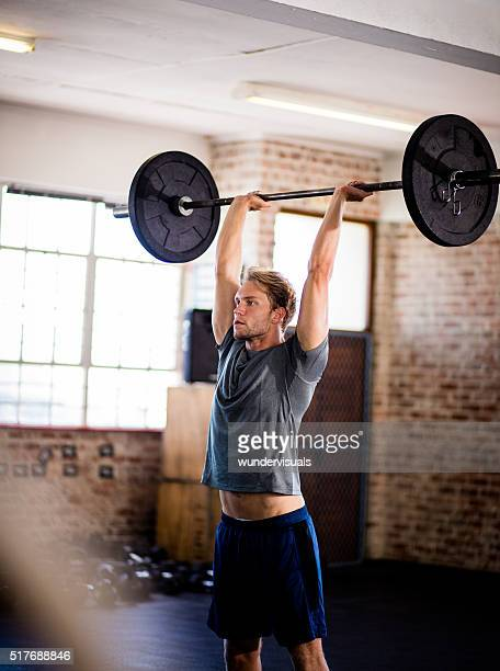 Young man doing power clean exercise during strength workout