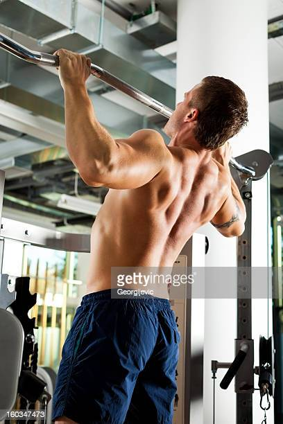 Young man doing pull-ups in gym.