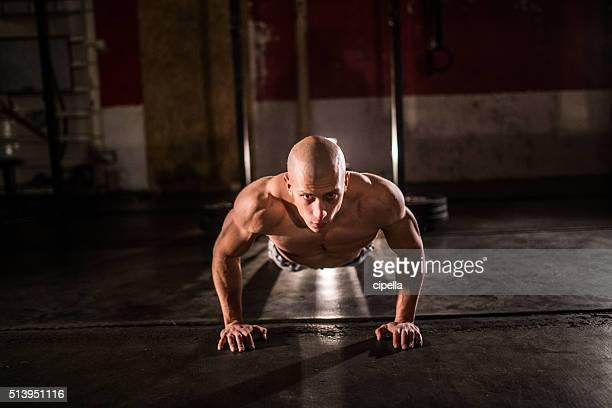 Junger Mann macht push-ups im Fitnessstudio