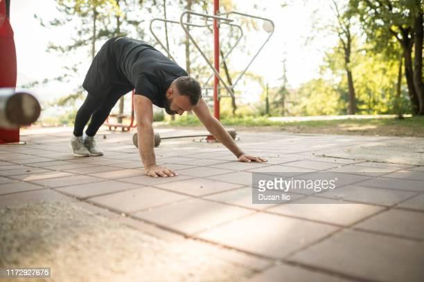 屋外でプッシュアップをしている若い男 - 自重トレーニング ストックフォトと画像